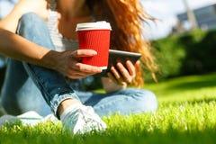 Giovane donna con un caffè da andare e ridurre in pani su un prato inglese Immagine Stock Libera da Diritti