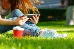 Giovane donna con un caffè da andare e ridurre in pani su un prato inglese Fotografia Stock Libera da Diritti