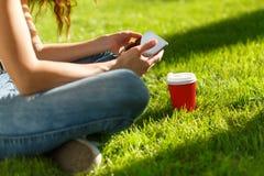 Giovane donna con un caffè da andare e ridurre in pani su un prato inglese Fotografie Stock Libere da Diritti