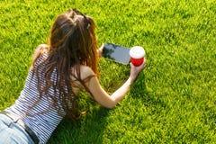 Giovane donna con un caffè da andare e ridurre in pani su un prato inglese Fotografie Stock