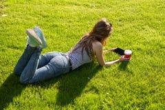 Giovane donna con un caffè da andare e ridurre in pani su un prato inglese Immagini Stock Libere da Diritti