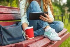 Giovane donna con un caffè da andare ridurre in pani pc su un banco Fotografia Stock Libera da Diritti