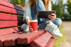 Giovane donna con un caffè da andare ridurre in pani pc su un banco Fotografia Stock