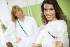 Giovane donna con un cane al veterinario fotografia stock