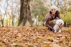 Giovane donna con un cane nella foresta di autunno fotografia stock libera da diritti