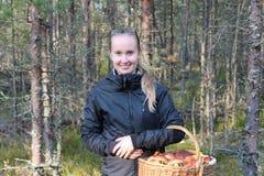 Giovane donna con un canestro dei funghi nella foresta Immagini Stock