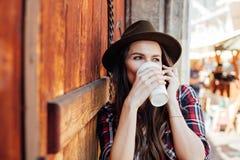 Giovane donna con un cappello accanto ad una vecchia porta di legno che parla al cel Fotografia Stock Libera da Diritti