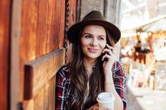 Giovane donna con un cappello accanto ad una vecchia porta di legno che parla al cel Immagine Stock Libera da Diritti