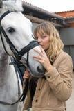 Giovane donna con un cavallo marrone Fotografia Stock