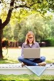 Giovane donna con un computer portatile che studia all'aperto Immagini Stock