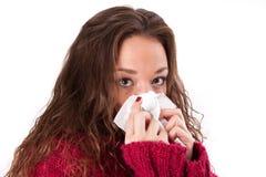 Giovane donna con un freddo ed i fazzoletti Immagine Stock