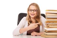 Giovane donna con un mucchio dei libri Immagine Stock