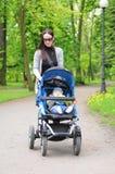 Giovane donna con un passeggiatore Immagine Stock Libera da Diritti