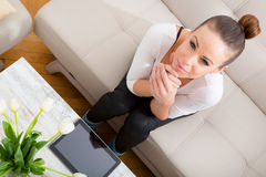 Giovane donna con un PC della compressa sul sofà Fotografia Stock