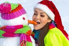 Giovane donna con un pupazzo di neve Fotografia Stock