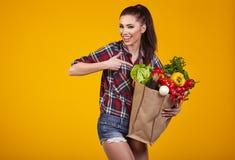 Giovane donna con un sacchetto di acquisto della drogheria Immagine Stock