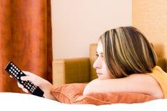 Giovane donna con un telecomando immagine stock