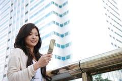 Giovane donna con un telefono mobile Immagini Stock Libere da Diritti