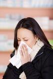 Giovane donna con un tessuto della carta di utilizzazione del freddo Fotografia Stock