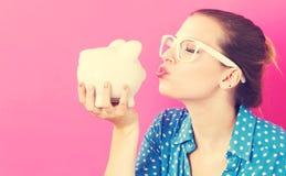 Giovane donna con una banca piggy fotografia stock libera da diritti