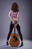 Giovane donna con una chitarra acustica su un fondo nero, posteriore Immagini Stock
