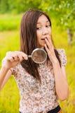 Giovane donna con una lente di ingrandimento Fotografia Stock Libera da Diritti