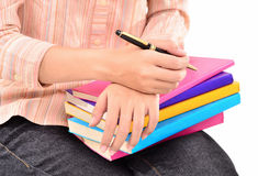 Giovane donna con una penna e una pila di libri Immagine Stock