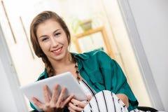 Giovane donna con una treccia facendo uso del computer della compressa fotografie stock libere da diritti