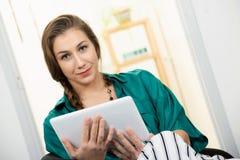 Giovane donna con una treccia facendo uso del computer della compressa fotografia stock libera da diritti