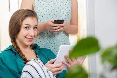 Giovane donna con una treccia facendo uso del computer della compressa fotografia stock