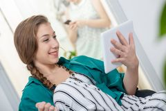 Giovane donna con una treccia facendo uso di un computer della compressa fotografie stock