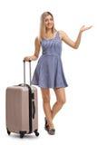 Giovane donna con una valigia che gesturing con la sua mano Fotografia Stock