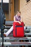Giovane donna con una valigia rossa Immagini Stock Libere da Diritti