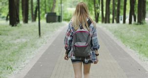 Giovane donna con uno zaino che va al parco di estate video d archivio