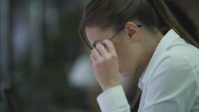 Giovane donna con vista difficile che mette sui vetri, segretario femminile sul lavoro video d archivio