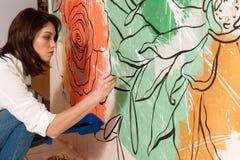 Giovane donna concentrata che decora parete con le pitture fotografia stock