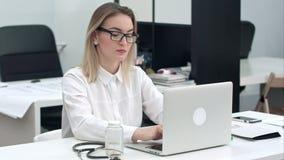 Giovane donna concentrata in vetri che scrive sul computer portatile alla sua scrivania video d archivio