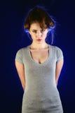 Giovane donna confusa in maglietta su fondo scuro Fotografia Stock Libera da Diritti