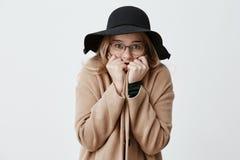 Giovane donna congelata che si avvolge nel fronte della copertura del cappotto con le mani che hanno occhi in pieno dello sforzo  Fotografia Stock Libera da Diritti