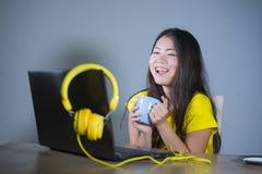 Giovane donna coreana asiatica graziosa e felice allo scrittorio che gode di Internet sul computer portatile che ride tè bevente  fotografia stock libera da diritti