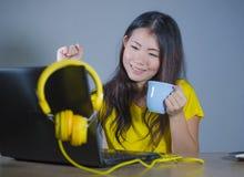 Giovane donna coreana asiatica graziosa e felice allo scrittorio che gode di Internet sul Cu bevente divertentesi allegro sorride Fotografie Stock Libere da Diritti