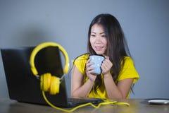 Giovane donna coreana asiatica graziosa e felice allo scrittorio che gode di Internet sul Cu bevente divertentesi allegro sorride Fotografie Stock