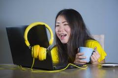 Giovane donna coreana asiatica graziosa e felice allo scrittorio che gode di Internet sul Cu bevente divertentesi allegro sorride Immagini Stock Libere da Diritti