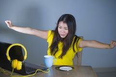 Giovane donna coreana asiatica graziosa e felice allo scrittorio che gode di Internet sul Cu bevente divertentesi allegro sorride Immagine Stock Libera da Diritti