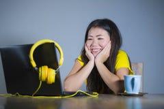 Giovane donna coreana asiatica graziosa e felice allo scrittorio che gode di Internet sul Cu bevente divertentesi allegro sorride Immagine Stock
