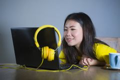 Giovane donna coreana asiatica graziosa e felice allo scrittorio che gode di Internet sul Cu bevente divertentesi allegro sorride Immagini Stock