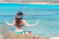 Giovane donna in costume da bagno verde e yoga black hat di pratiche sulla spiaggia del mar Mediterraneo qigong e libertà immagine stock