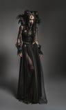 Giovane donna in costume nero di fantasia Fotografie Stock