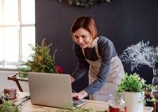 Giovane donna creativa in un negozio di fiore, facendo uso del computer portatile Una partenza dell'affare del fiorista fotografia stock libera da diritti