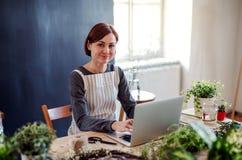Giovane donna creativa in un negozio di fiore, facendo uso del computer portatile Una partenza dell'affare del fiorista fotografia stock